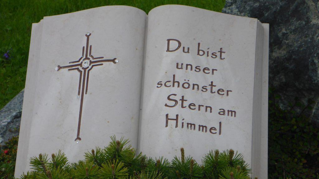"""Aufgeschlagenes Buch aus Stein: """"Du bist unser schönster Stern am Himmel""""."""