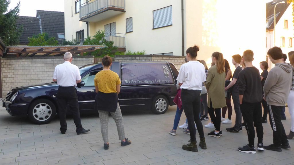 Die Firmlinge stehen um das Überführungsfahrzeug, welches durch Herrn Scherer erklärt wird.