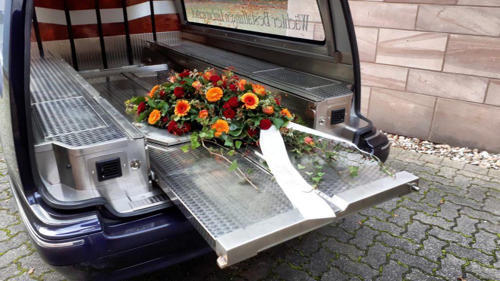 Ausladen des Sargdeckelbuketts mit anschließendem ablegen auf dem Grab.