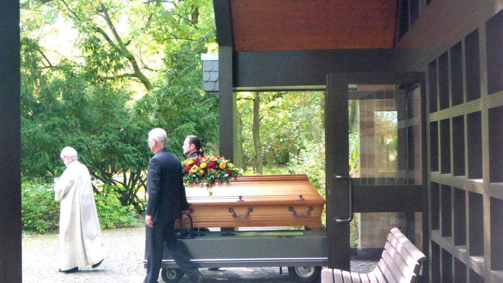 Der Sarg des Verstorbenen wird zum Überführungsfahrzeug gefahren, die Trauergäste folgen.