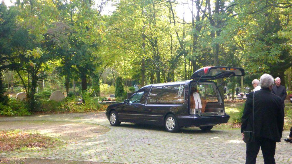 Die Trauergäste versammeln sich am Überführungsfahrzeug.