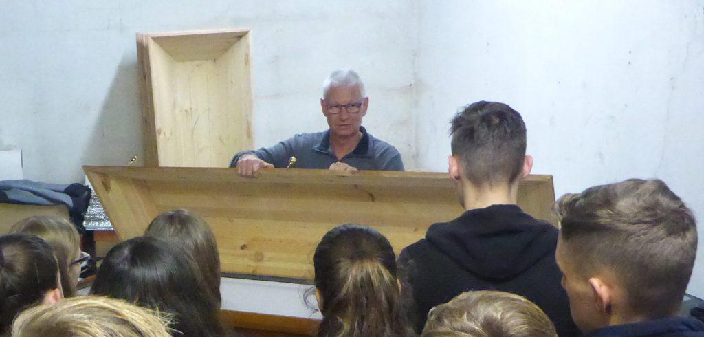 Herr Scherer hebt den Deckel eines ausgeschlagenen Sarges an und gewährt den Jugendlichen einen Einblick in den Sarg.