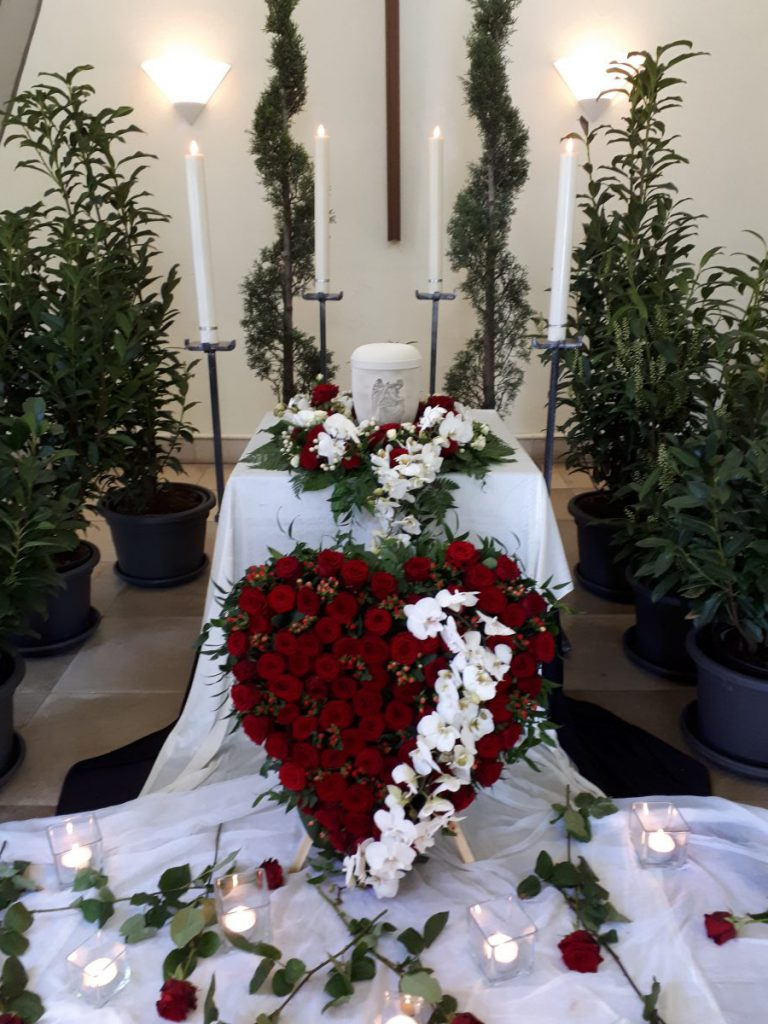 Dekoration einer Urne mit einem rotem Herz aus Rosen