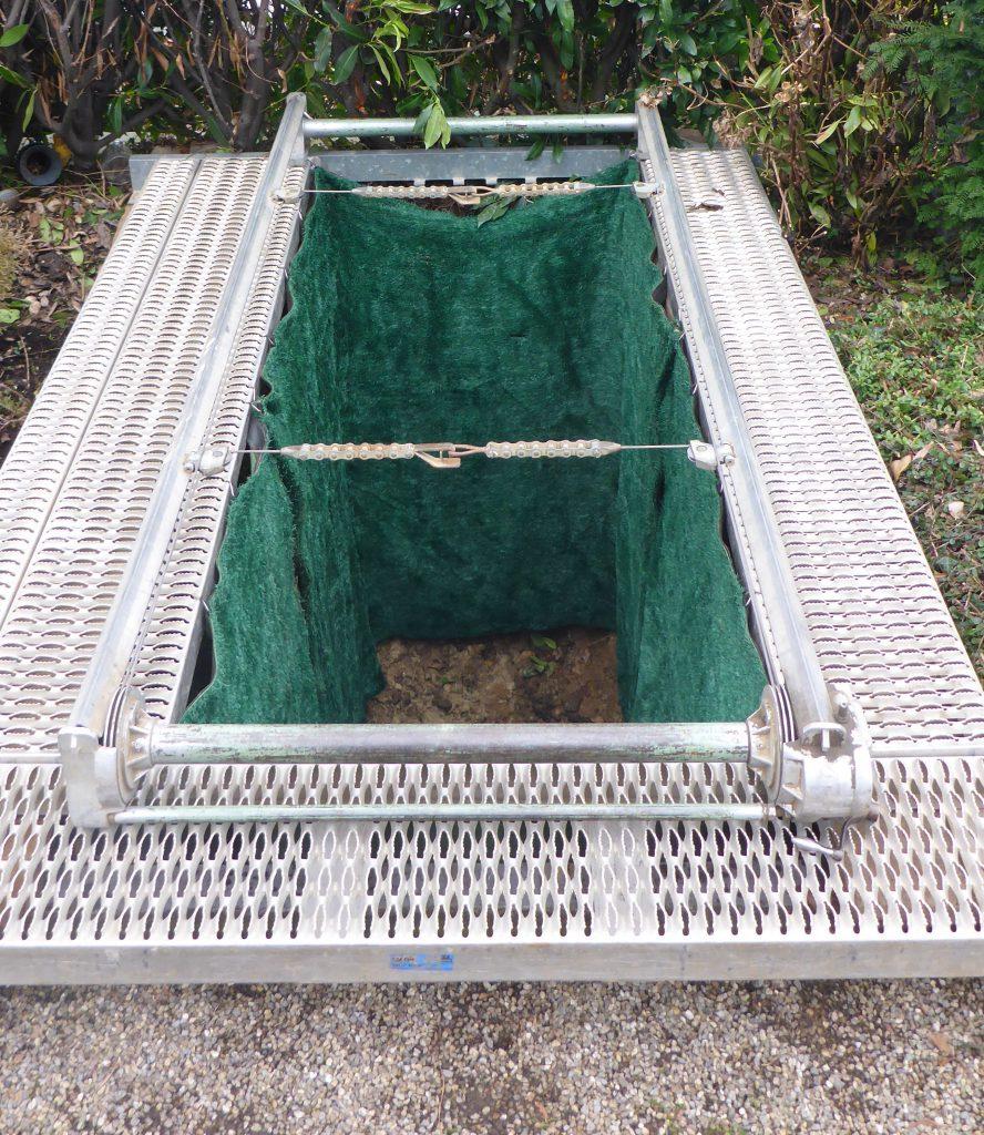 Vorbereitetes Grab mit Laufsteg, Grabmatten und Ablassvorrichtung für die Beisetzung eines Sarges.