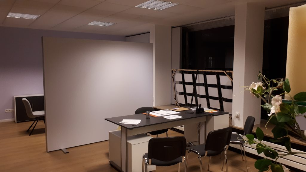 Bild auf den Schreibtisch mit abgetrenntem Besprechungsbereich im Hintergrund..