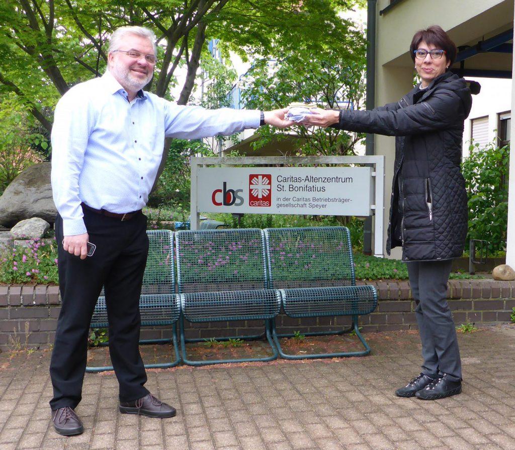 Christian Hassa, Leiter des Caritas Altenzentrum Limburgerhof und Dagmar Scherer bei der Übergabe der Gesichtsmasken.